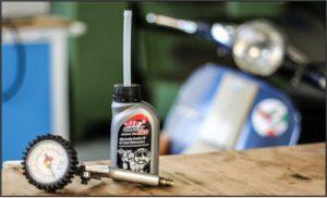 Offene Ölkanne und Gerät zur Reifendruckkontrolle bereitgestellt für den Service an einer Vespa oder Simson